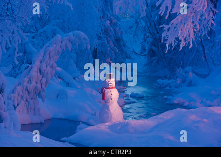 Snowman wearing black scarf top hat standing next small stream in hoarfrost covered forest twilight Russian Jack - Stock Photo