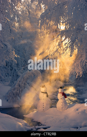 Snowman couple standing next stream sunrays shining through fog hoar frosted trees in background Russian Jack Springs - Stock Photo