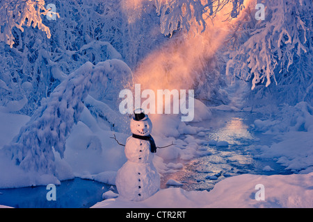 Snowman standing next stream sunrays shining through fog hoar frosted trees in background Russian Jack Springs Park - Stock Photo
