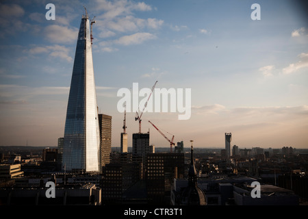 The Shard in the London skyline shining in early evening sunset. The tower is the tallest building on northern europe. - Stock Photo