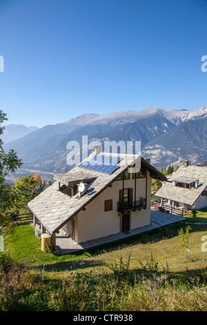 Alpine house with solar panels in the ski resort of Sauze d'Oulx, Piemonte, Italy - Stock Photo