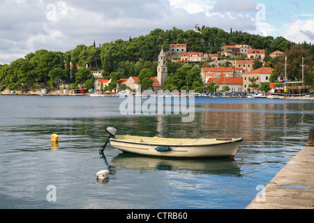 A small boat moored in a scenic medieval fishing village along the coast of Croatia. - Stock Photo