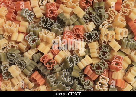 Italian pasta of durum wheat semolina with tomato and spinach in form of teddy bears. Funny for children. - Stock Photo