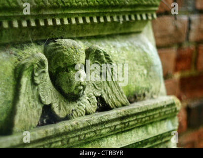 Cherub on old headstone in graveyard. - Stock Photo