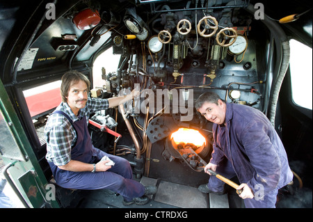 Train driver and fireman in the cab  of Southern Railway Steam Locomotive 'West Counry' Class Pacific 4-6-2 Number - Stock Photo