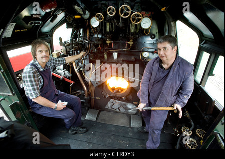 Train driver and fireman in the cab  of Southern Railway Steam Locomotive 'West Country' Class Pacific 4-6-2 Number - Stock Photo