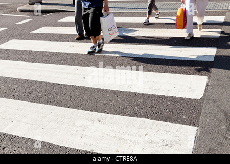 People crossing the road on a zebra crossing, England, UK - Stock Photo