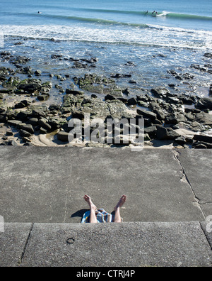 The legs of a sunbather at Alexandra Headland in Queensland - Stock Photo