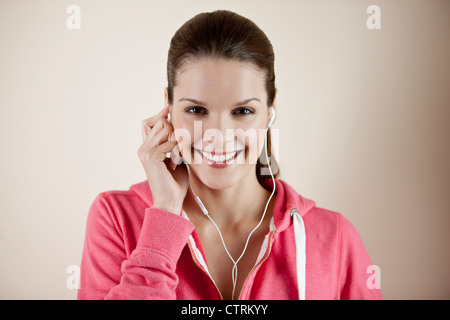 A young woman wearing fitness clothing and earphones, listening to music - Stock Photo