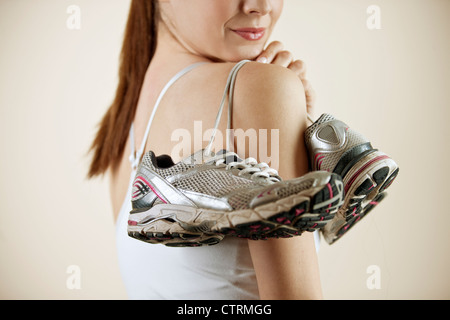 A young woman holding a pair of training shoes over her shoulder, close-up