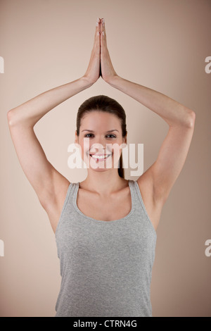 A young woman practicing yoga, tree pose - Stock Photo