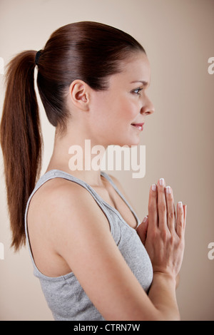 A young woman practicing yoga, hands in prayer position - Stock Photo