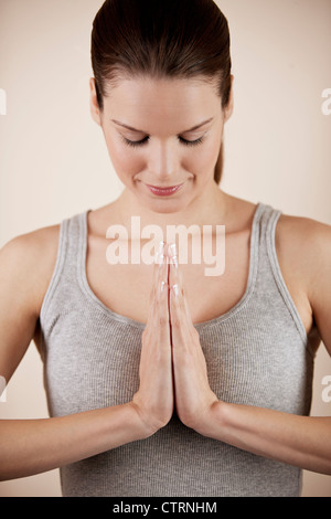 A young woman meditating, hands in prayer position - Stock Photo