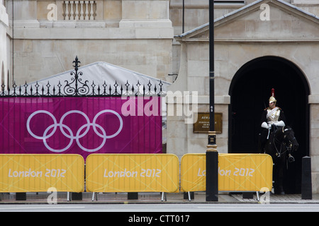 Olympic rings on a banner outside Horse Guards where a soldier from the Household Cavalry sits motionless on his - Stock Photo