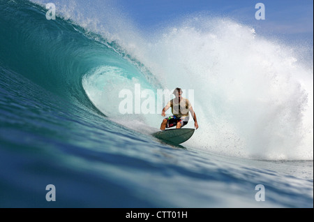 Australian surfer riding a large hollow wave on a remote reef break on Nias Island, Sumatra. - Stock Photo