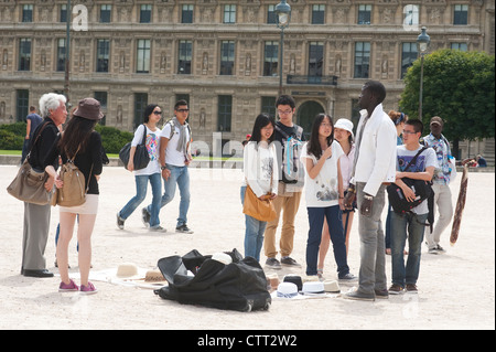 A group of tourists next to  a street vendor in Paris, France - Stock Photo