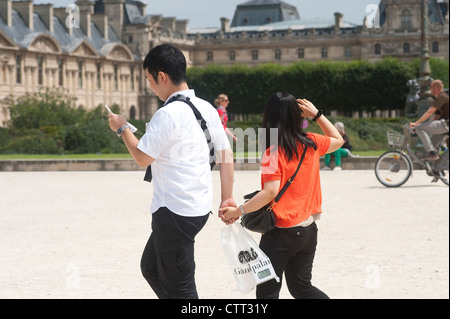 Paris, France - Asian couple hand on hand visiting the city. - Stock Photo