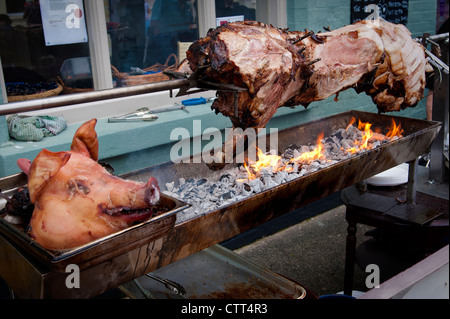 Hog spit roast on a barbecue with a pig's head in the foreground - Stock Photo