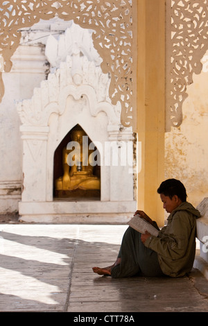 Myanmar, Burma. Man Reading at Shwezegon (Shwezigon) Pagoda, near Bagan. - Stock Photo
