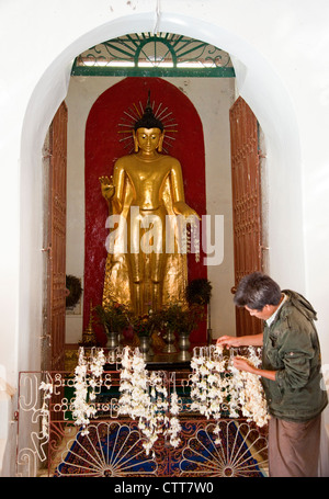 Myanmar, Burma, Shwezegon (Shwezigon) Pagoda, near Bagan. A Worshiper leaving a garland of flowers. - Stock Photo