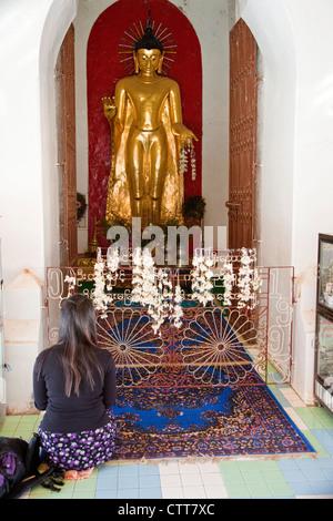 Myanmar, Burma, Shwezegon (Shwezigon) Pagoda, near Bagan. Young Woman with Backpack Kneels in front of Buddha Statue. - Stock Photo