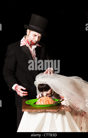 A zombie groom jokingly shoves his brides face into a platter of