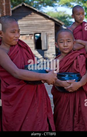 Myanmar, Burma. Bagan. Young Novice Monks Holding their Begging Bowls. - Stock Photo