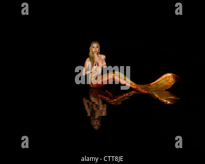 Young blond mermaid sitting in a reflection pool in Virginia Beach, Virginia. - Stock Photo