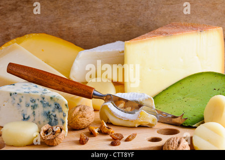 Background with cheese variety on a wooden board - Stock Photo
