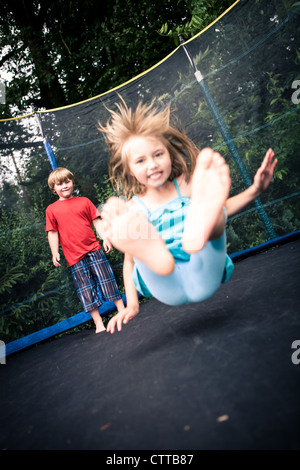 jupming kids on the trampoline in the garden - Stock Photo