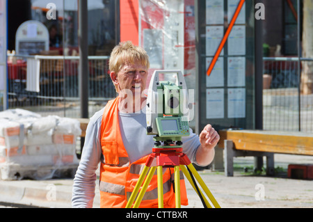Geodesist land surveyor measures track construction site with modern up to date theodolite wearing orange signal - Stock Photo