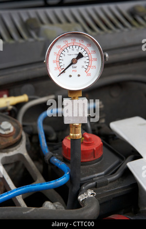 using a compression tester to measure the compression on a car engine cylinder showing zero reading - Stock Photo