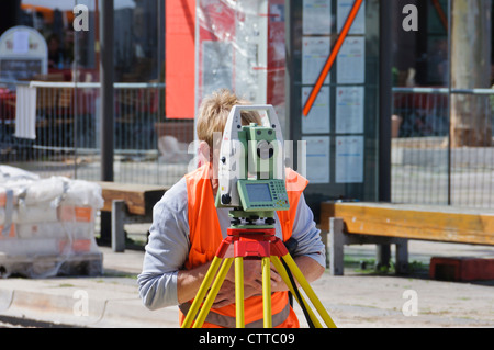 Geodesist land surveyor measures track construction site with modern up to date Leica theodolite with orange signal - Stock Photo