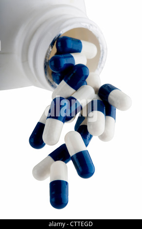Blue and White capsules falling out of prescription bottle - Stock Photo
