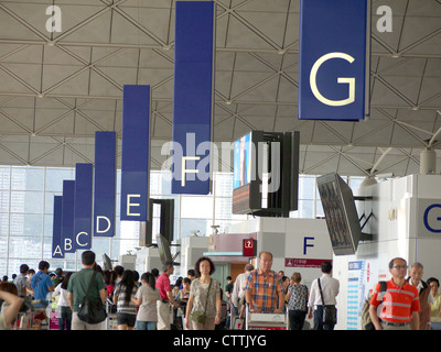 View along a row of letters identifying departure islands at Hong Kong international airport - Stock Photo