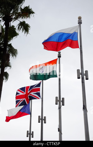Four national flags on flag poles flying on a windy day. - Stock Photo