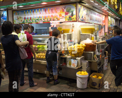 Typical Hong Kong Fast Food Kiosk on a street at night selling freshly squeezed cool fruit drinks - Stock Photo