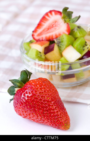 Strawberry and fruit salad in white plate on tablecloth, close up - Stock Photo