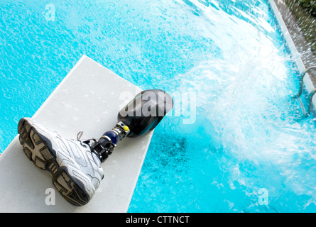 Cannonball splash in a pool with prosthetic leg left on diving board. - Stock Photo