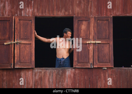 A man in the window of his house in the village of PWE SAR KONE - INLE LAKE, MYANMAR - Stock Photo