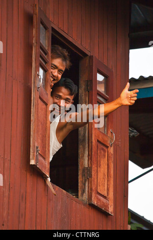 Young men say hello from a window in the village of PWE SAR KONE - INLE LAKE, MYANMAR - Stock Photo
