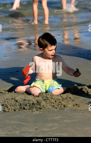 Young boy sitting on the sandy beach makes a sandcastles at Weymouth - Stock Photo