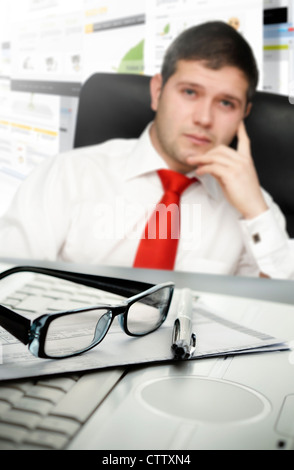 Young businessman at office with selective focus on glasses and pen - Stock Photo