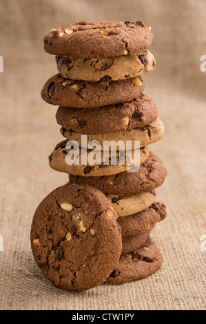 Stacked mixed Cookies on brown background - Stock Photo