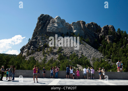 Tourists view Mt. Rushmore from the main viewing deck, Mount Rushmore National Monument, South Dakota, United States - Stock Photo