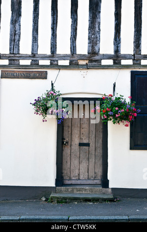 Hanging Baskets on Either Side of Wooden Door of Timber Framed Building in Lavenham - Stock Photo