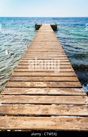 wooden pier on coast of Coral beach of Red Sea in Aqaba, Jordan - Stock Photo