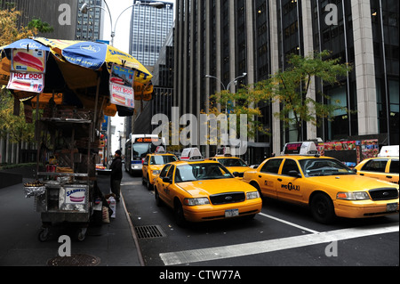 Autumn trees view skyscrapers, sidewalk snack-stall, bus, five yellow taxis waiting West 50th Street at 6th Avenue, - Stock Photo