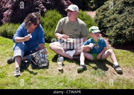 American family enjoys impromptu picnic on grass in bright summer sunshine at Saturday farmers market Edmonds Washington - Stock Photo