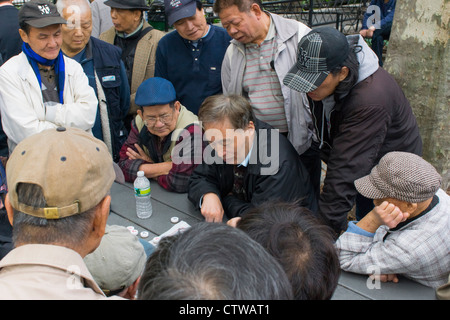 Men playing Chinese checkers at a table in Columbus Park, Chinatown, New York City - Stock Photo